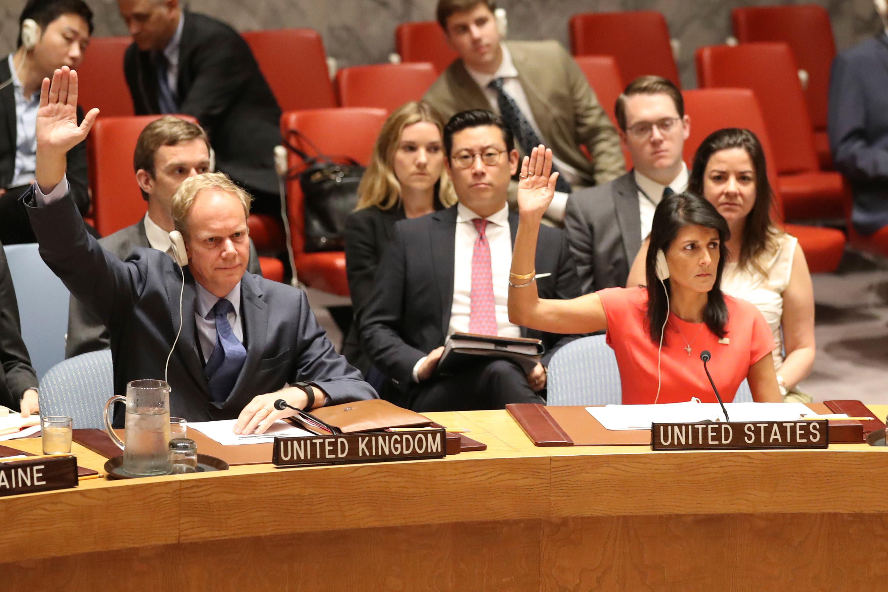 British Ambassador to the United Nations Matthew Rycroft, left, and U.S. Ambassador to the United Nations Nikki Haley vote during a Security Council meeting on a new sanctions resolution that would increase economic pressure on North Korea to return to negotiations on its missile program, Saturday, Aug. 5, 2017 at U.N. headquarters. (AP Photo/Mary Altaffer)