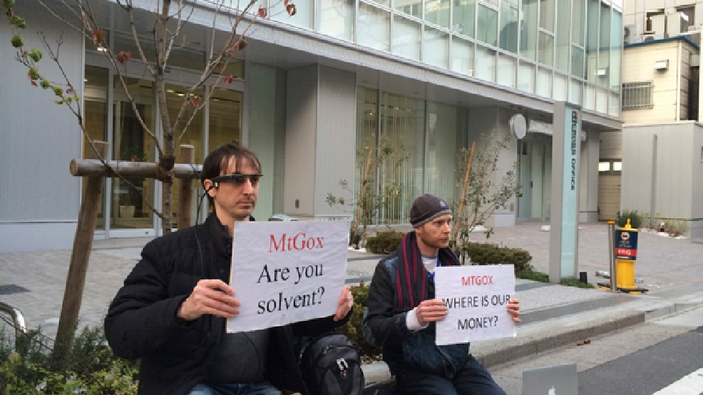 Bitcoin trader Kolin Burges, right, of London and American Aaron (only his first name was given) hold protest signs as they conduct a sit-in in front of the office tower housing Mt. Gox in Tokyo Tuesday, Feb. 25, 2014. (AP Photo/Kaori Hitomi)
