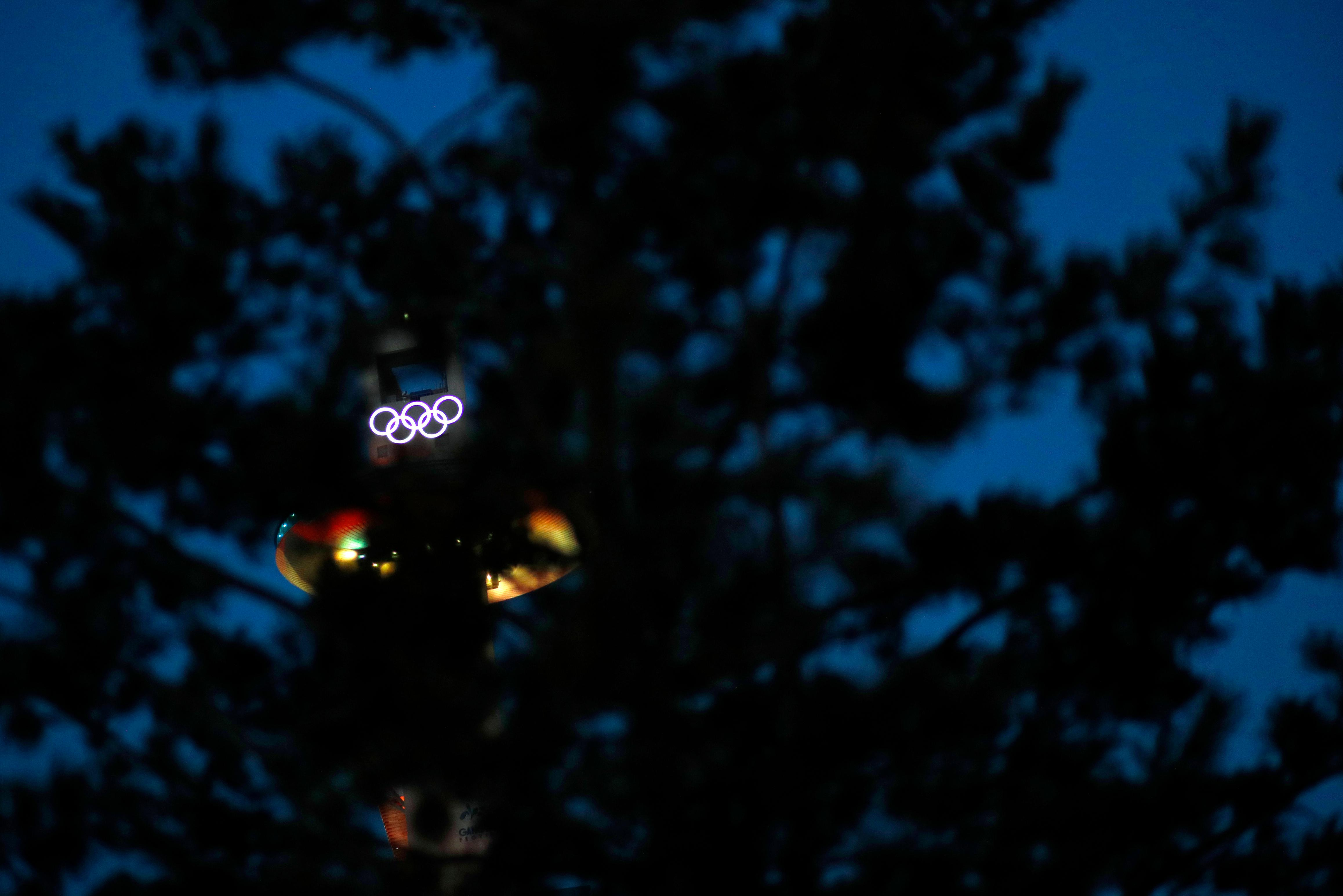 Illuminated Olympic rings atop the Alpensia Ski Jumping Center shine through tree branches at the Alpensia resort prior to the 2018 Winter Olympics in Pyeongchang, South Korea, Friday, Feb. 2, 2018. (AP Photo/Patrick Semansky)