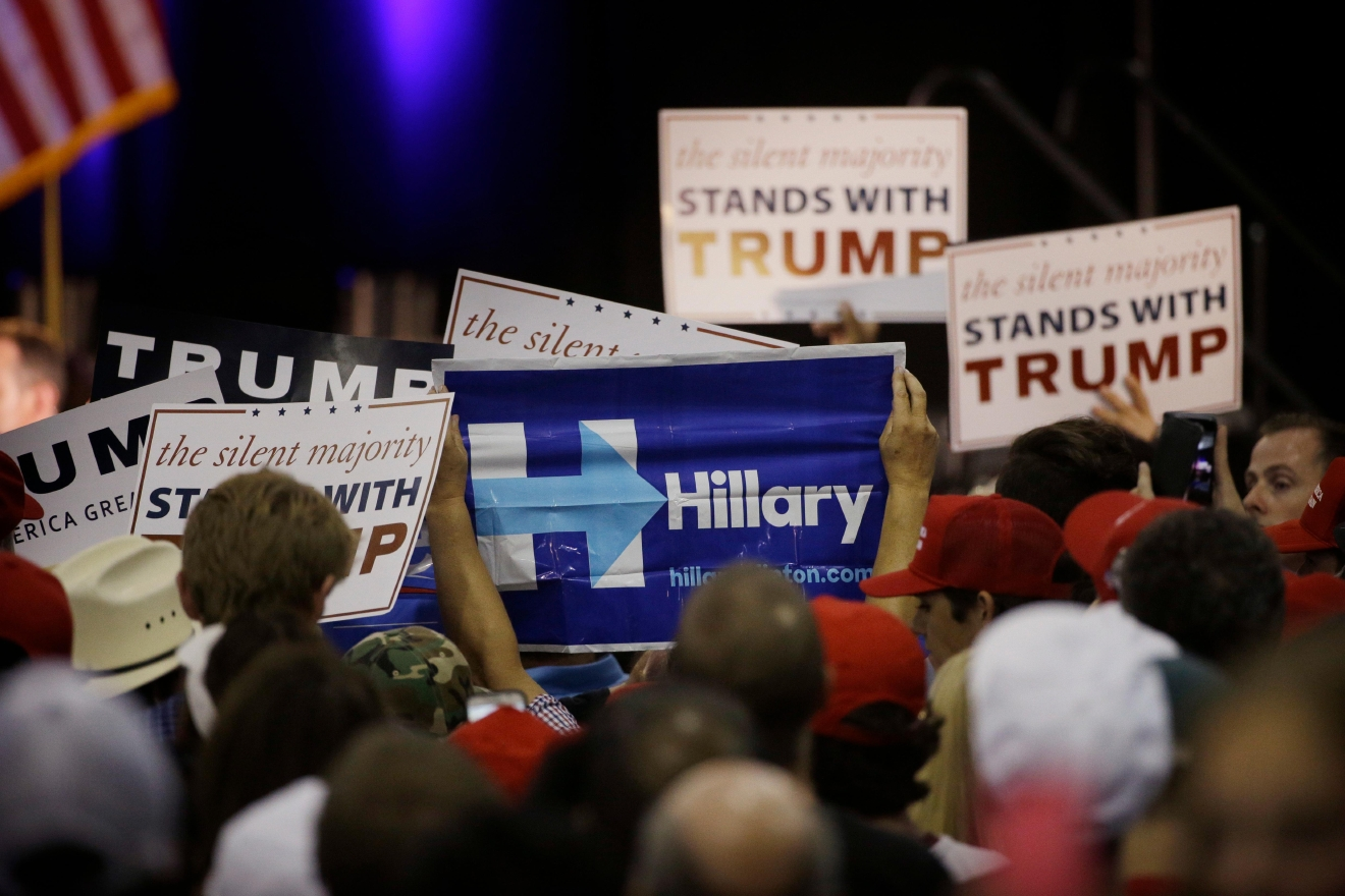 A woman holds up a sign for Democratic presidential candidate Hillary Clinton during a rally for Republican presidential candidate Donald Trump, Thursday, June 2, 2016, in San Jose, Calif. (AP Photo/Jae C. Hong)