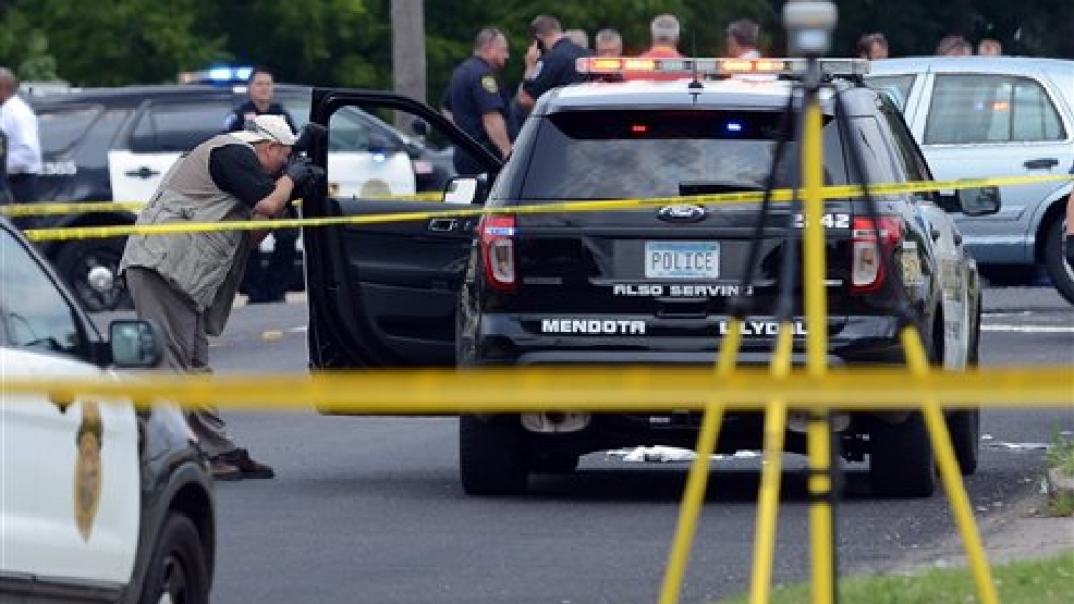 A officer with the Minnesota Bureau of Criminal Apprehension photographs an vechicle that was driven by a Mendota Heights Police officer who was shot during a traffic stop in West St. Paul on Wednesday, July 30, 2014. A potential suspect in the shooting of a police officer in West St. Paul has been captured near the suburb of Woodbury. (AP Photo/The St. Paul Pioneer Press, Ben Garvin)