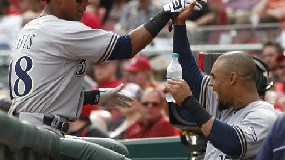 Milwaukee Brewers' Khris Davis (18) is congratulated by Carlos Gomez (27) after Davis hit a solo home run off Cincinnati Reds starting pitcher Alfredo Simon (31) during the fourthinning of a baseball game, Sunday, May 4, 2014, in Cincinnati. (AP Photo/David Kohl)