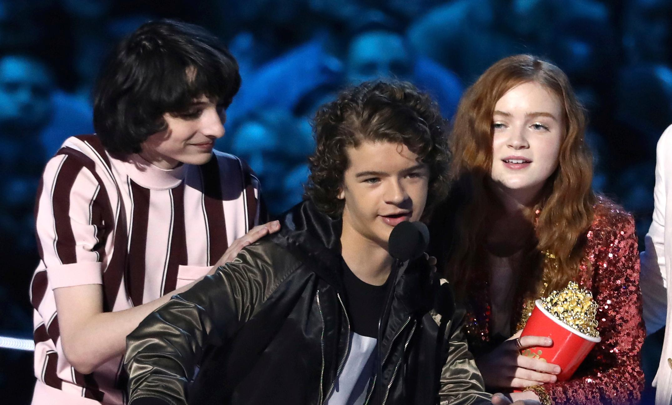 "In this Saturday, June 16, 2018, photo, Finn Wolfhard, from left, Gaten Matarazzo and Sadie Sink accept the award for best show for ""Stranger Things"" at the MTV Movie and TV Awards at the Barker Hangar in Santa Monica, Calif. (Photo by Matt Sayles/Invision/AP)"