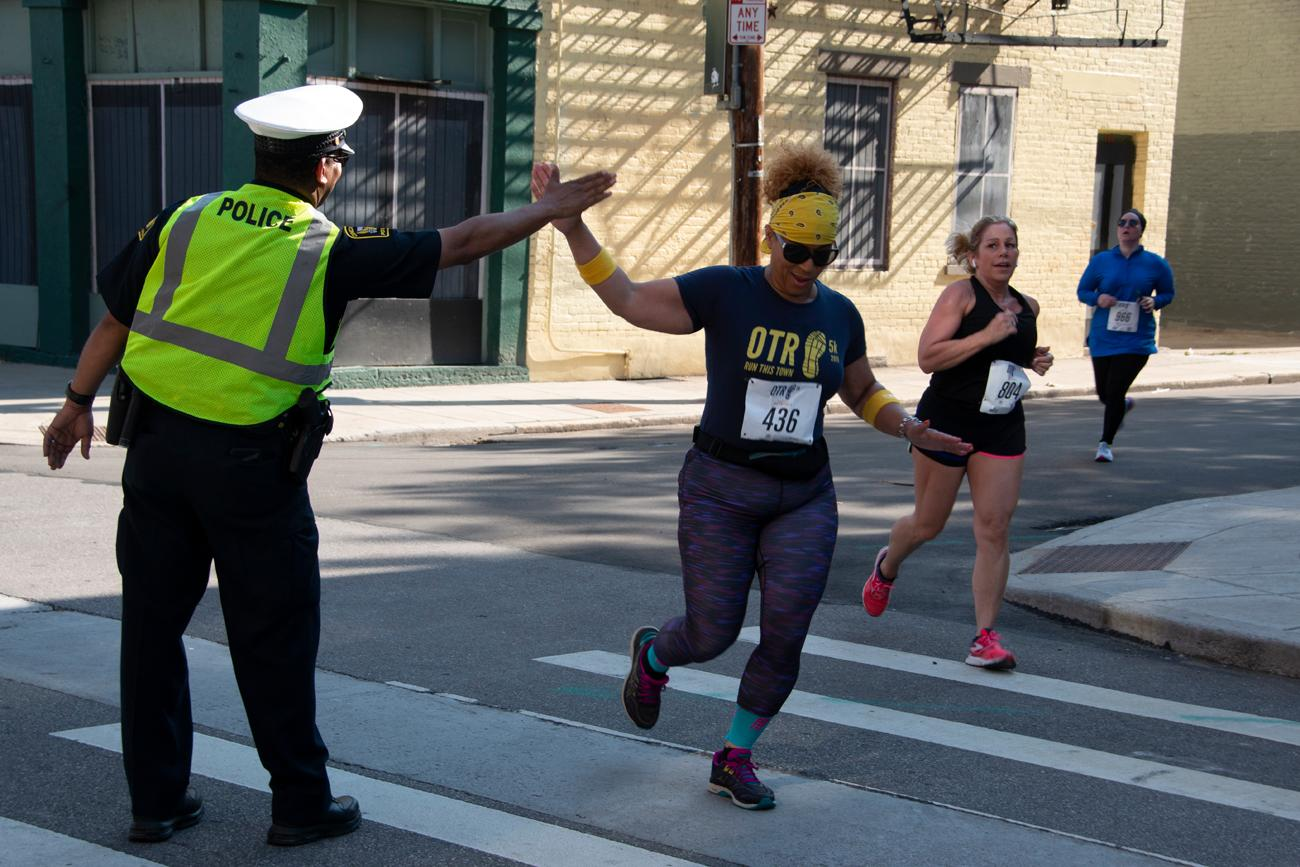 Laconia Smith high-fives a police officer as she runs by. / Image: Dr. Richard Sanders // Published: 5.19.19