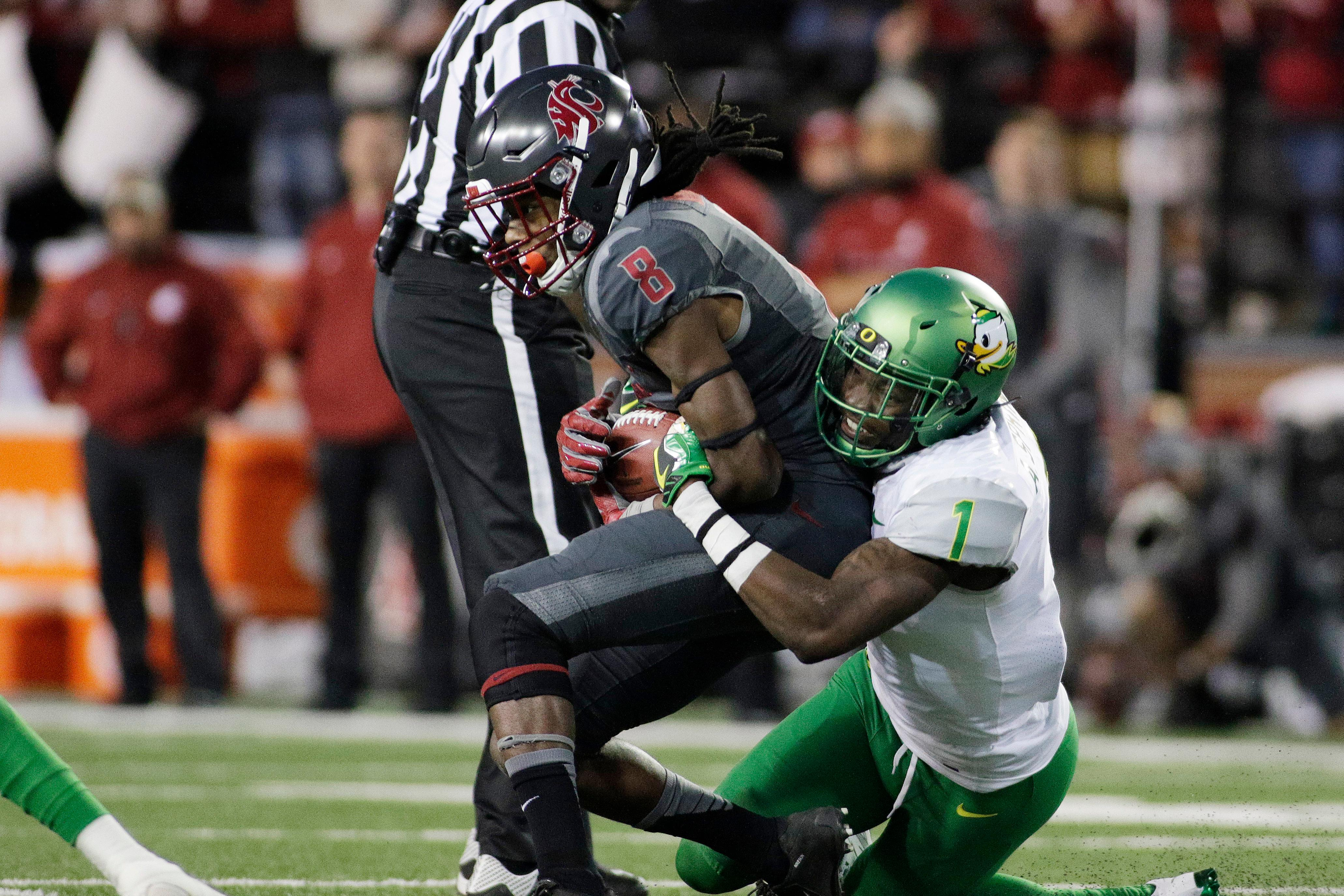 FILE - In this Oct. 1, 2016, file photo, Oregon defensive back Arrion Springs (1) brings down Washington State wide receiver Tavares Martin Jr. (8) during the second half of an NCAA college football game, in Pullman, Wash. Springs was selected to the 2017 AP All-Conference Pac-12 team announced Thursday, Dec. 7, 2017. (AP Photo/Young Kwak, File)