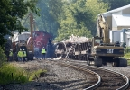 Workers clean up after a train derailment in Slinger, Wis., Monday, July 21, 2014. A southbound Canadian National train struck several Wisconsin & Southern Railroad cars around 8:30 p.m. Sunday at a rail crossing in Slinger, Wis., according to Patrick Waldron, a Canadian National spokesman. The derailment injured at least two people and spilled thousands of gallons of fuel that prompted the evacuation of dozens of homes, but evacuees were allowed to return around 1:30 a.m. Monday, Slinger Fire Chief Rick Hanke said. (AP Photo/Milwaukee Journal-Sentinel, Gary Porter)
