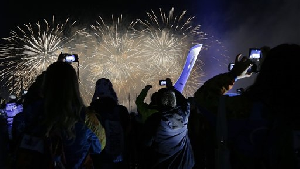 Visitors to Olympic Park record the fireworks show behind the Olympic cauldron after the flame was extinguished at the end of the closing ceremonies at the 2014 Winter Olympics, Sunday, Feb. 23, in Sochi, Russia. (AP Photo/Julie Jacobson)