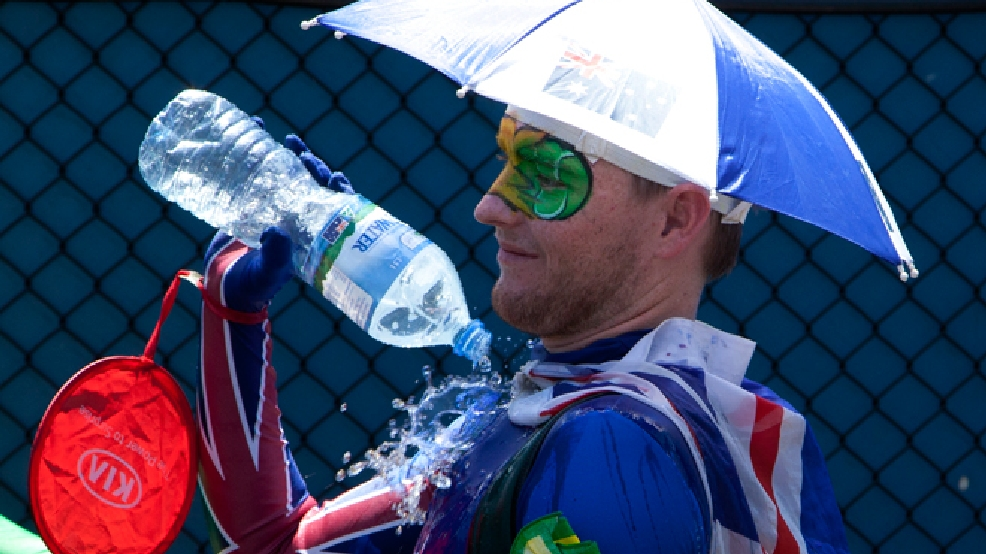 A spectators pours water over himself to cool down as play was suspended when organizers implemented the Extreme Heat policy during second round matches at the Australian Open tennis championship in Melbourne, Australia, Thursday, Jan. 16, 2014.  (AP Photo/Joshua Baker)