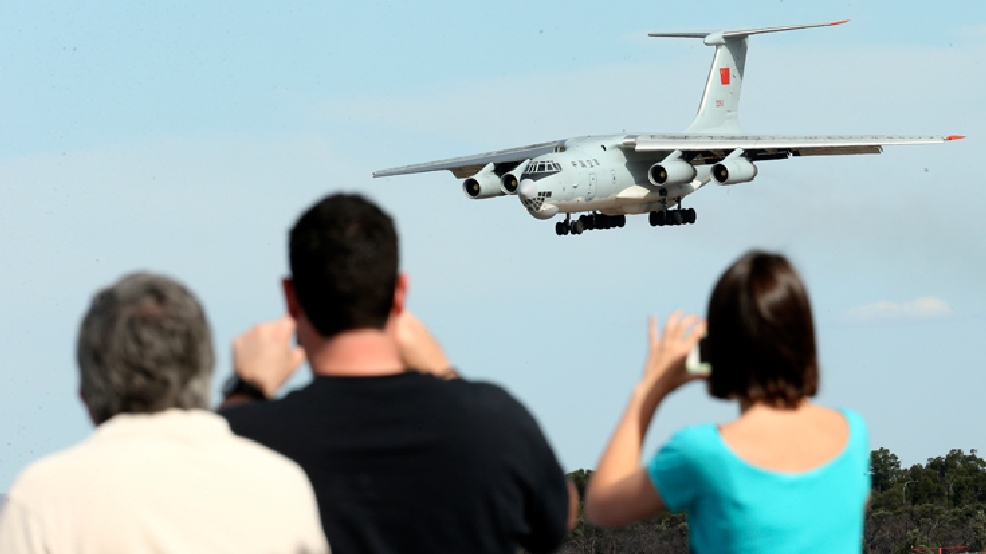 Spectators take photos of a Chinese Ilyushin IL-76 aircraft as it comes in for a landing at Perth International Airport after returning from the ongoing search operations for missing Malaysia Airlines Flight 370 in Perth, Australia, Thursday, April 10, 2014. With hopes high that search crews are zeroing in on the missing Malaysian jetliner's crash site, ships and planes hunting for the aircraft intensified their efforts Thursday after equipment picked up sounds consistent with a plane's black box in the deep waters of the Indian Ocean. (AP Photo/Rob Griffith)