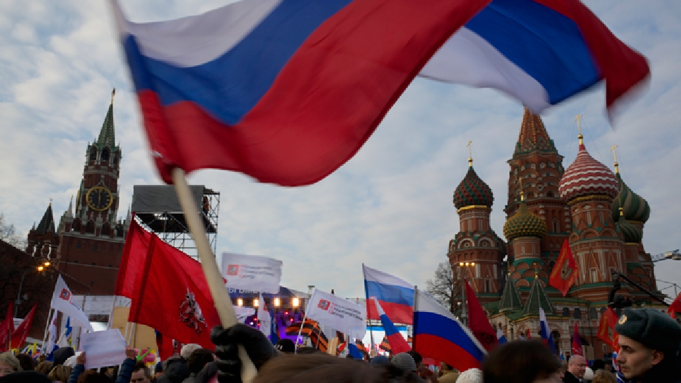 Pro-Putin demonstrators wave Russian national flags as they gather towards to Red Square in Moscow, Russia, Friday, March 7, 2014, with Spassky Tower, left, and St. Basile Cathedral, right, are in the background. (AP Photo/Alexander Zemlianichenko)