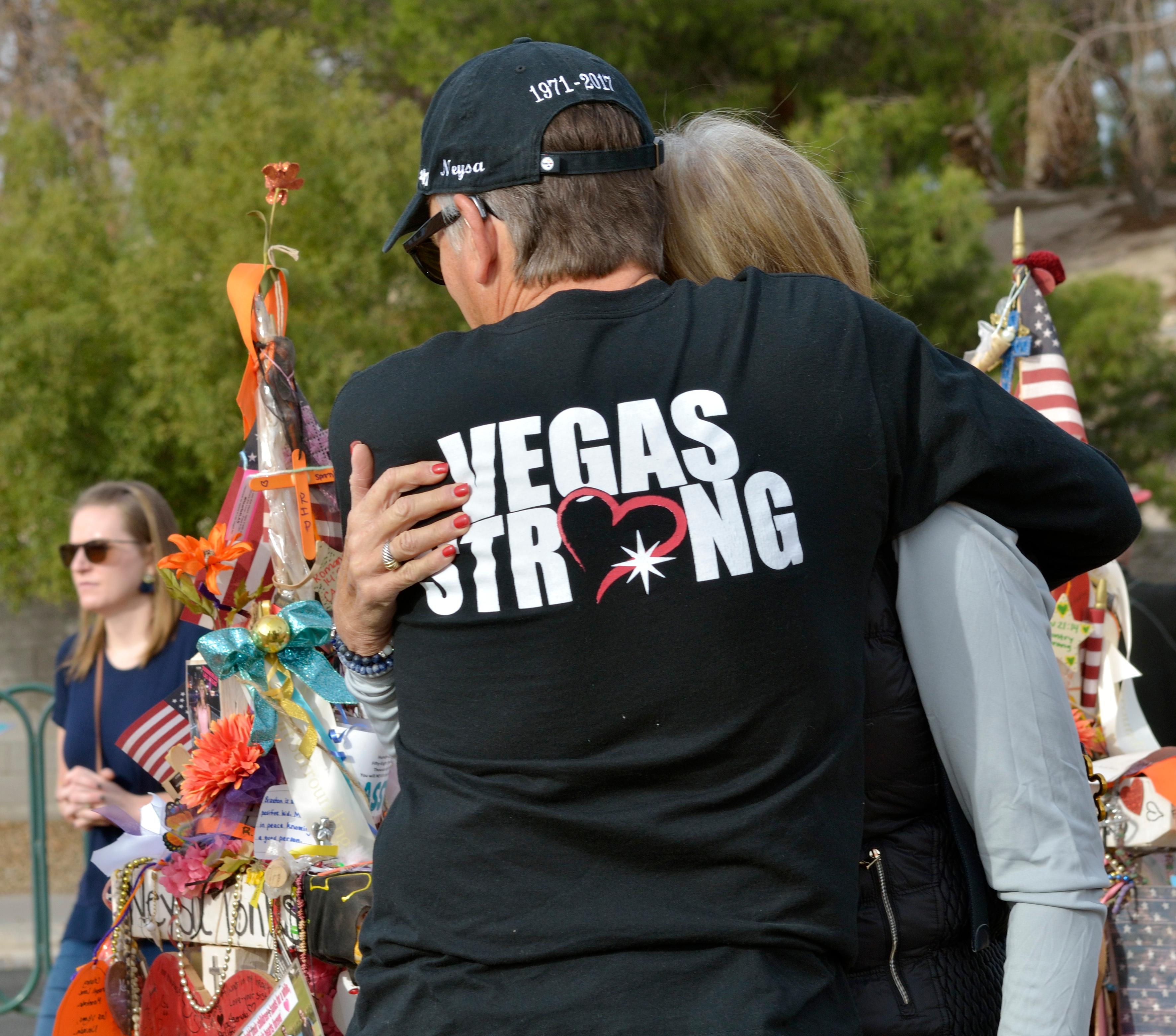 "Chris and Debbie Davis hug near a memorial cross for their daughter Neysa Tonks during ""Greg Zanis Day"" at the Welcome to Fabulous Las Vegas sign on the Las Vegas Strip on Sunday, Nov. 12, 2017. Zanis, a carpenter from Aurora, Ill., was recognized by the Clark County Commision for creating 58 crosses memorializing those who died during the Route 91 Harvest festival shooting on Oct. 1. The crosses were later moved to the Clark County Museum for its permanent collection. [Bill Hughes/Las Vegas News Bureau]"