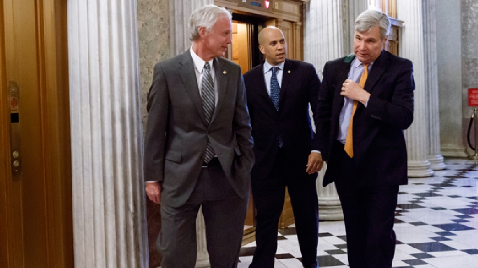 Sen. Ron Johnson, R-Wis., left, Sen. Cory Booker, D-N.J., center, and Sen. Sheldon Whitehouse, D-R.I., head to the chamber during the vote on restoring jobless benefits for the long-term unemployed, legislation that expired late last year, at the Capitol in Washington, Monday, April 7, 2014. (AP Photo/J. Scott Applewhite)