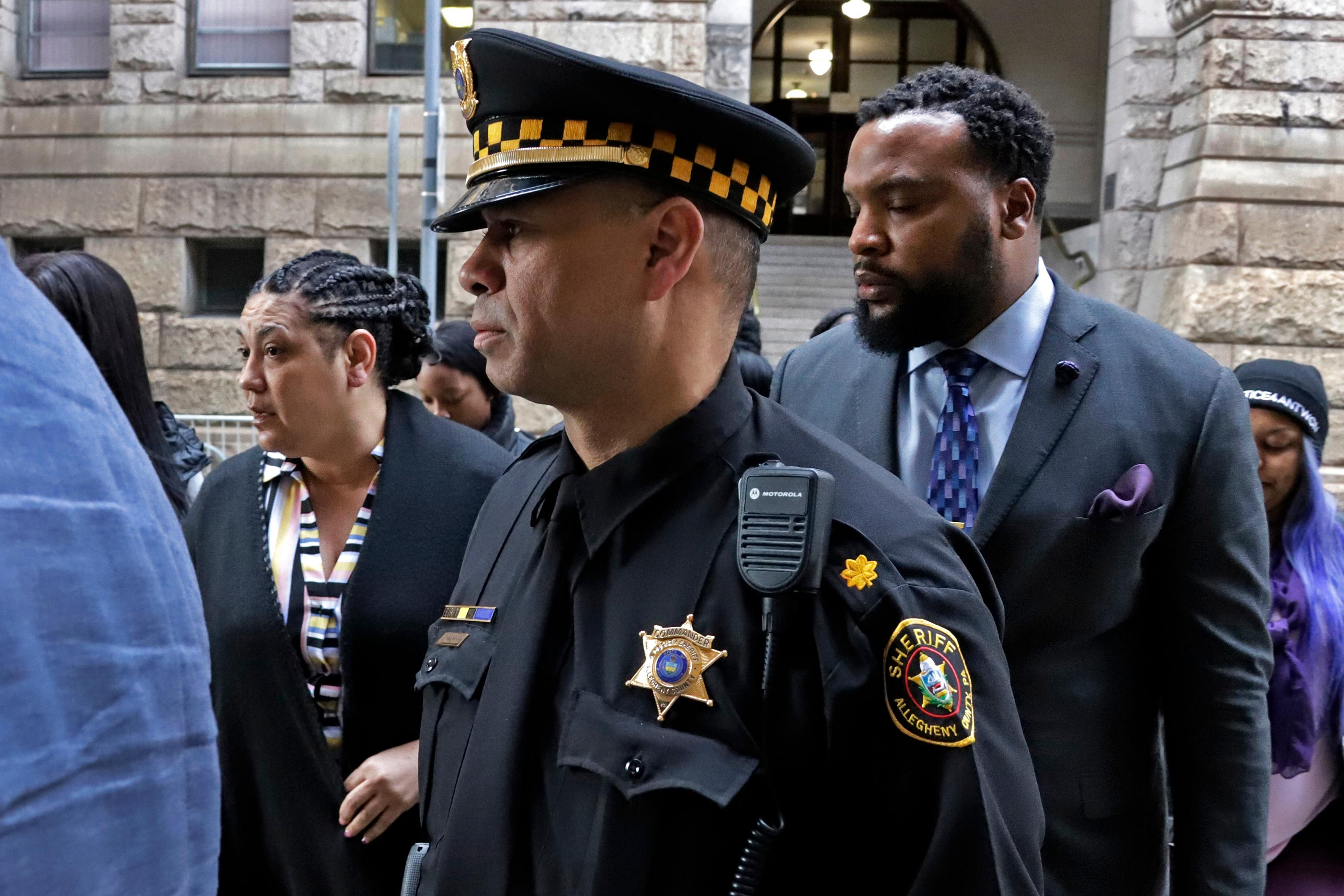 Michelle Kenney, left, the mother of Antwon Rose II, leaves the Allegheny County Courthouse with her lawyer S. Lee Merritt, right, after day two of the trial for Michael Rosfeld, a former police officer in East Pittsburgh, Pa., Wednesday, March 20, 2019. Rosfeld is charged with homicide in the fatal shooting of Antwon Rose II as he fled during a traffic stop on June 19, 2018. (AP Photo/Gene J. Puskar)
