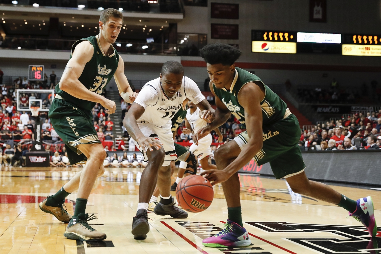 South Florida's Tulio Da Silva, right, steals the ball from Cincinnati's Gary Clark (11) as Ruben Guerrero (33) looks on in the first half of an NCAA college basketball game, Sunday, Jan. 29, 2017, in Cincinnati. (AP Photo/John Minchillo)