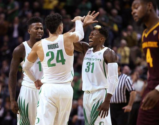 Oregon's Jordan Bell, left, Dillon Brooks and Dylan Ennis celebrate Oregon taking the lead, as Arizona State's Torian Graham leaves the court for a timeout in the closing minutes of an NCAA college basketball game Thursday, Feb. 2, 2017, in Eugene, Ore. (AP Photo/Chris Pietsch)
