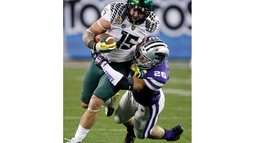 Oregon tight end Colt Lyerla (15) is tackled by Kansas State linebacker Jarell Childs (26) during the second half of the Fiesta Bowl NCAA college football game, Thursday, Jan. 3, 2013, in Glendale, Ariz. (AP Photo/Paul Connors)