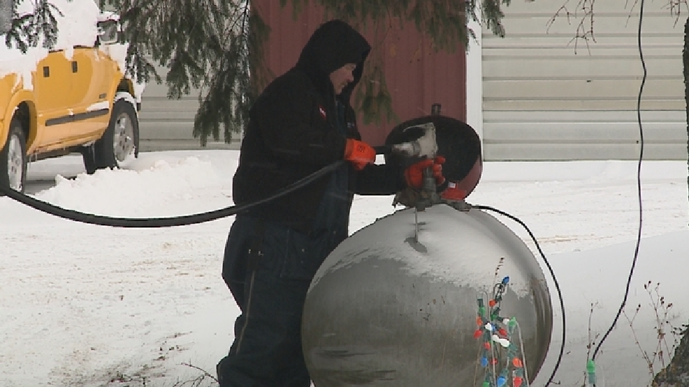 A worker fills a propane tank on Monday, Dec. 23, 2013.