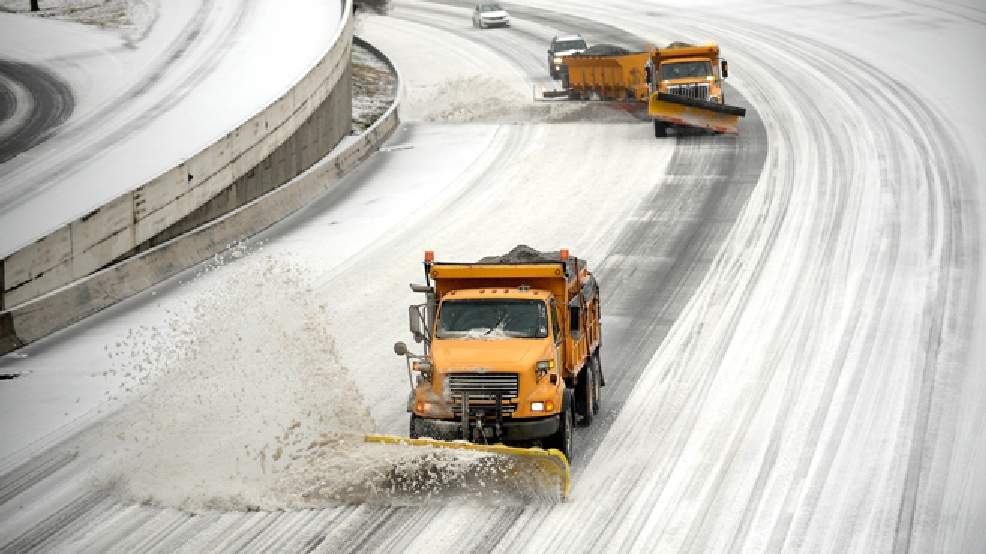 Snow plows clear downtown lanes on Interstate 75/85 during a winter storm on Wednesday, Feb. 12, 2014, in Atlanta. (AP Photo/David Tulis)