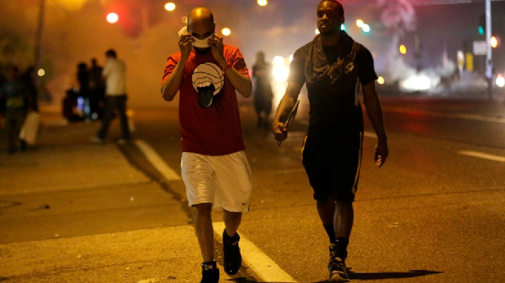 Men walk away from a cloud of tear gas during a protest Monday, Aug. 18, 2014, for Michael Brown, who was killed by a police officer Aug. 9 in Ferguson, Mo. Brown's shooting has sparked more than a week of protests, riots and looting in the St. Louis suburb. (AP Photo/Charlie Riedel)