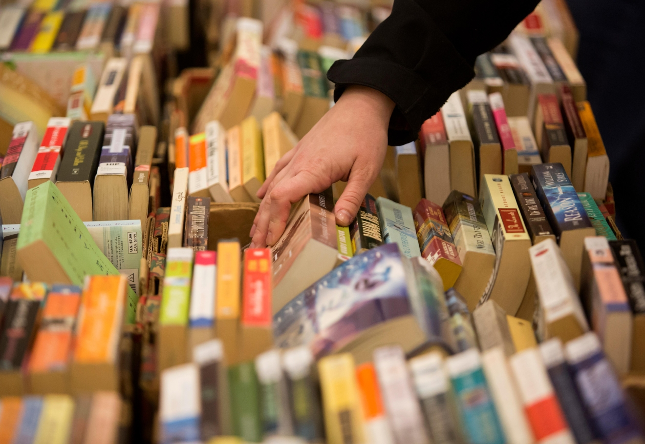 A book enthusiasts sorts through some of the 100,000 titles for sale at the Big Book Sale 2017, put on by the Friends of The Seattle Public Library. (Sy Bean / Seattle Refined)