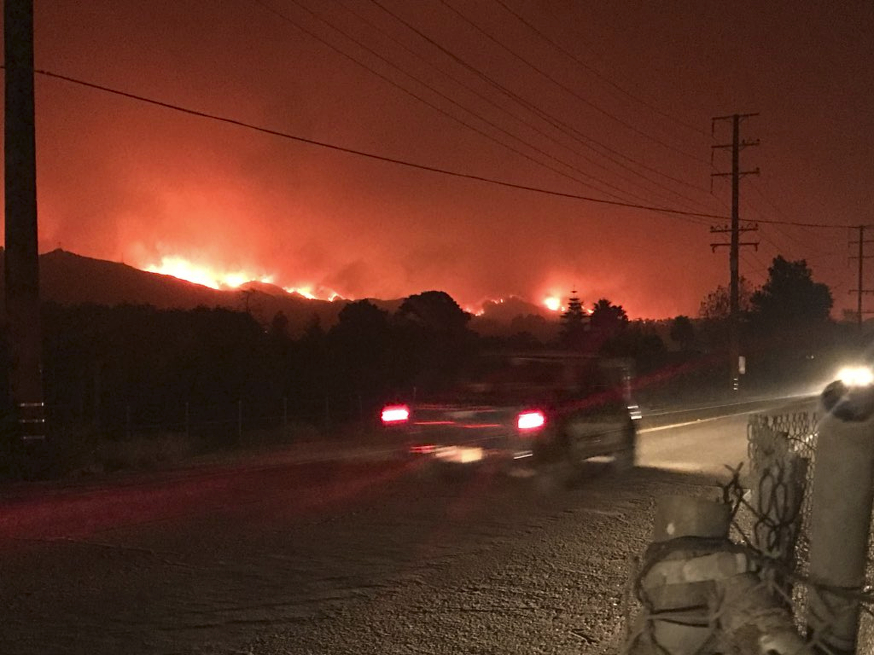 In this early morning Sunday, Dec. 10, 2017 photo released by Santa Barbara County Fire Department, flames are seen behind Carpinteria, Calif. A flare-up on the western edge of Southern California's largest and most destructive wildfire sent residents fleeing Sunday, as wind-fanned flames churned through canyons and down hillsides toward coastal towns. Crews with help from water-dropping aircraft saved several homes as unpredictable gusts sent the blaze churning deeper into foothill areas northwest of Los Angeles that haven't burned in decades. New evacuations were ordered in Carpinteria, a seaside city in Santa Barbara County that has been under fire threat for days. (Mike Eliason/Santa Barbara County Fire Department via AP)
