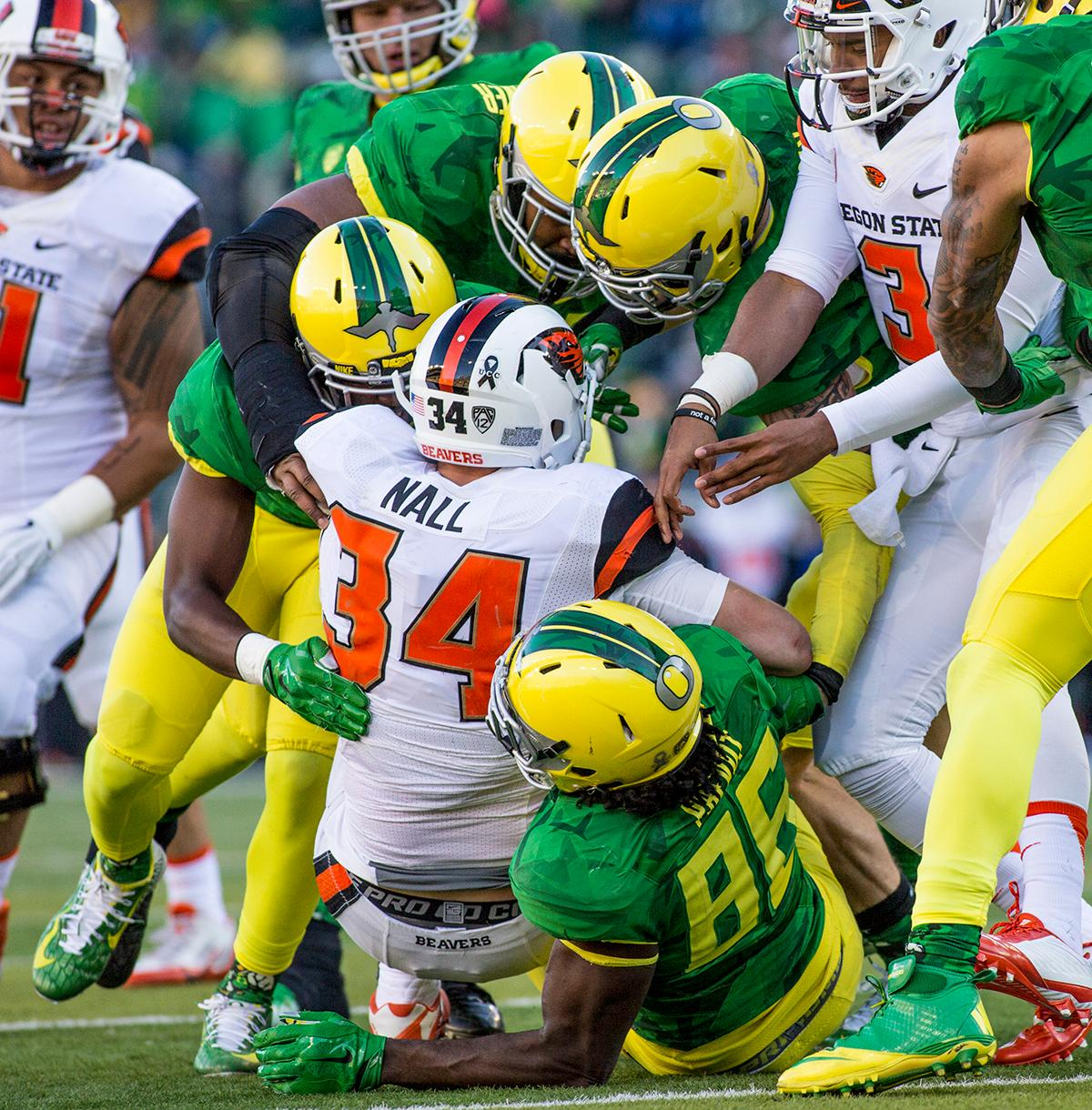 Oregon Ducks defense team tackles Oregon State Beavers Ryan Nall (#34) in the Civil War game in Autzen Stadium. At the half the Ducks led the Beavers 31 - 7. Photo by Katie Pietzold, Oregon News Lab