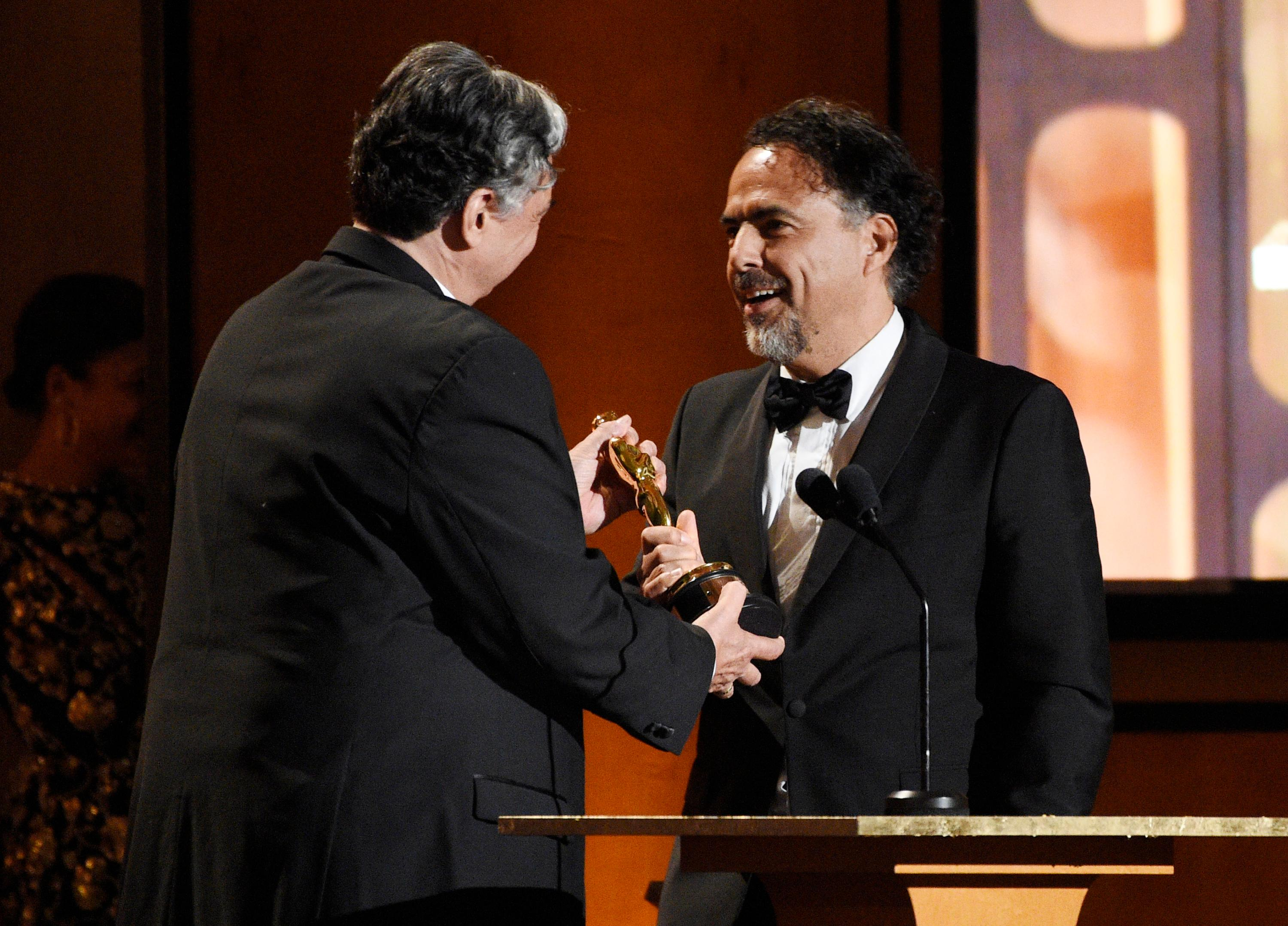"Mexican director Alejandro Gonzalez Inarritu, right, accepts a Special Award Oscar from presenter Gregory Nava for his virtual reality installation ""Carne y Arena (Virtually present, Physically invisible)"" at the 2017 Governors Awards at The Ray Dolby Ballroom on Saturday, Nov. 11, 2017, in Los Angeles. (Photo by Chris Pizzello/Invision/AP)"