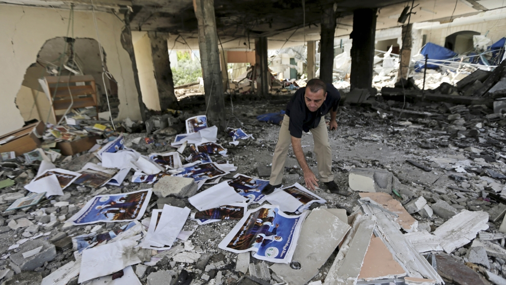 A Palestinian searches the rubble of a center for disabled, that is littered with posters soliciting donations to support the Al Mabara association for handicapped run by Hamas, after an Israeli missile strike in Beit Lahiya, in the northern Gaza Strip, Saturday, July 12, 2014. Israeli airstrikes on Gaza hit a mosque and a center for the disabled where two women were killed Saturday, raising the Palestinian death toll from the offensive to more than 125, Palestinian officials said, in an offensive that showed no signs of slowing down. (AP Photo/Adel Hana)