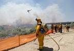 Firefighters watch from a ridge as a helicopter drops retardant on a out-of- control wild fire Tuesday, May 13, 2014, in San Diego. (AP Photo)