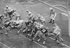 With seconds remaining in the NFL Championship Game Dec. 31, 1967, at Lambeau Field, quarterback Bart Starr (15) bulls way behind the Packers' play leader - the center - and key blocker Jerry Kramer (64), who is delivering key block to Dallas' tackle Jethro Pugh (75).