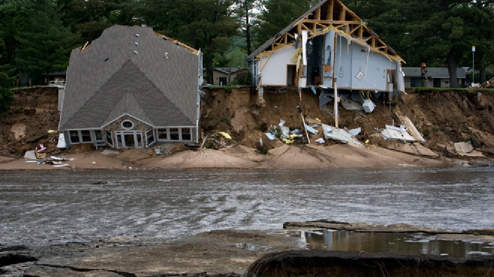 Two houses fall into an emptied Lake Delton Tuesday, June 10, 2008, in Lake Delton, Wis., after the 267-acre lake overflowed and drained Monday. (AP Photo/Andy Manis)