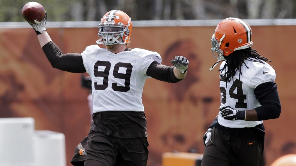 Cleveland Browns outside linebacker Paul Kruger (99) catches a pass tipped by Quentin Groves during a voluntary minicamp workout at the NFL football team's facility in Berea, Ohio, Thursday. (AP Photo/Mark Duncan)
