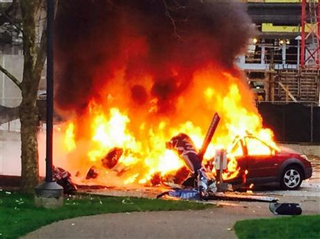 In this photo provided by KOMO-TV, a car burns at the scene of a helicopter crash outside the KOMO-TV studios near the space needle in Seattle on Tuesday, March 18, 2014.