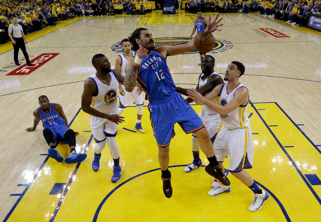 Oklahoma City Thunder's Steven Adams (12) grabs a rebound next to Golden State Warriors' Klay Thompson, right, and Festus Ezeli (31) during the first half in Game 2 of the NBA basketball Western Conference finals Wednesday, May 18, 2016, in Oakland, Calif. (AP Photo/Marcio Jose Sanchez)