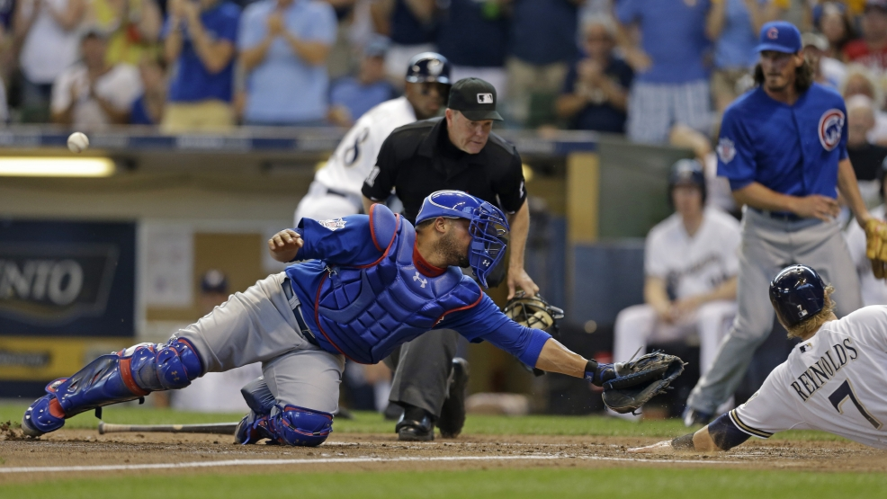 Milwaukee Brewers' Mark Reynolds (7) scores as Chicago Cubs' Wellington Castillo tries to tag him without the ball during the third inning of a baseball game on Sunday, June 1, 2014, in Milwaukee. Reynolds scored on Lyle Overbay's triple. (AP Photo/Jeffrey Phelps)