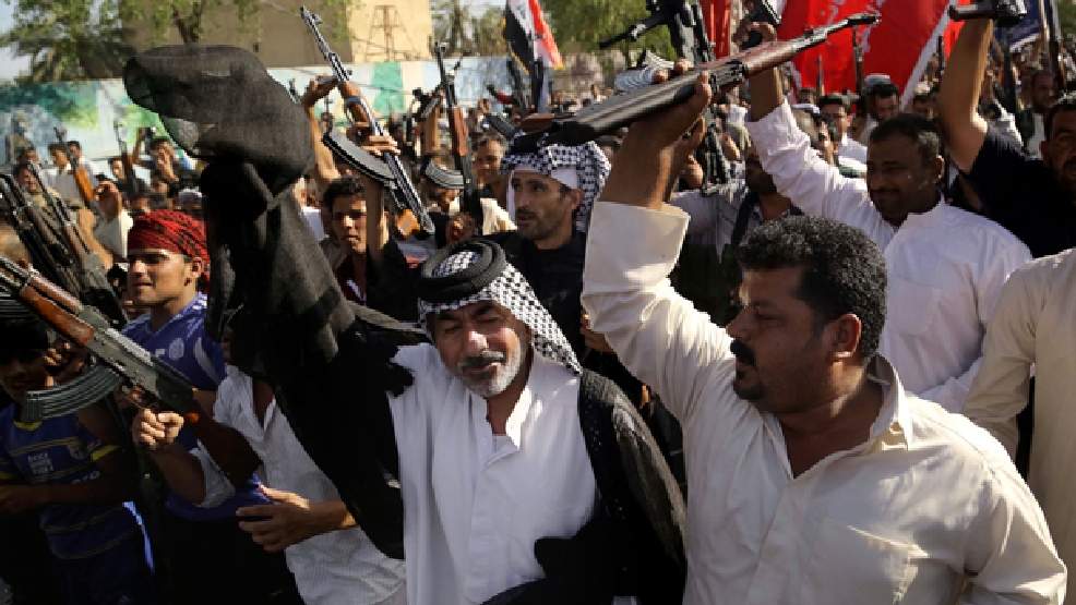 Shiite tribal fighters raise their weapons against the al-Qaida-inspired Islamic State of Iraq and the Levant (ISIL) in Basra, Iraq's second-largest city, 340 miles (550 kilometers) southeast of Baghdad, Iraq, Monday, June 16, 2014. Sunni militants captured a key northern Iraqi town along the highway to Syria early on Monday, compounding the woes of Iraq's Shiite-led government a week after it lost a vast swath of territory to the insurgents in the country's north. (AP Photo/Nabil Al-Jurani)
