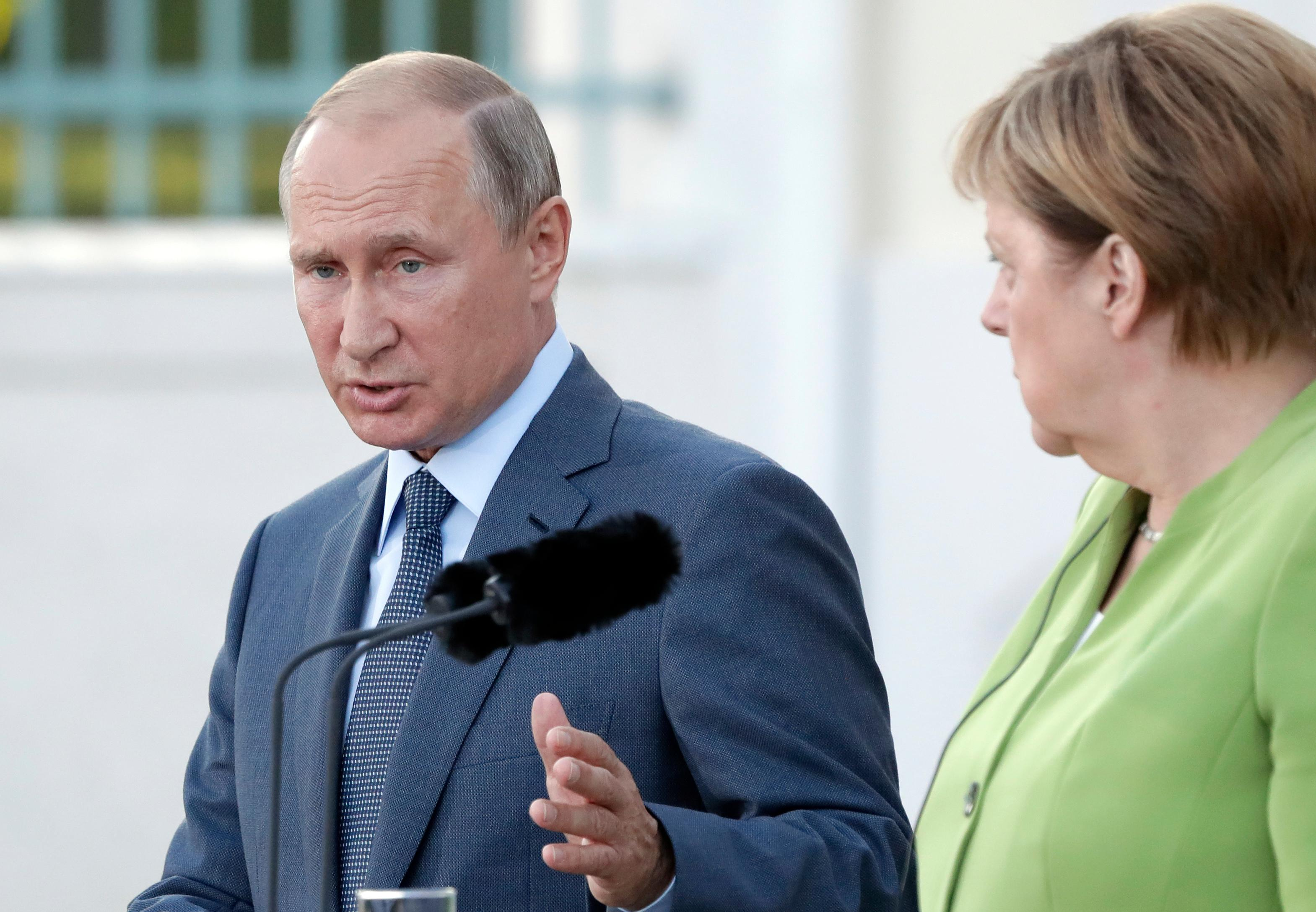 German Chancellor Angela Merkel and the President of Russia, Vladimir Putin{ } address the media during a joint statement Aug. 18. (AP Photo/Michael Sohn)